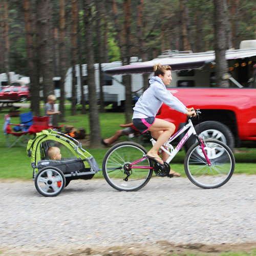 Woman On Bike With Child In Trailer