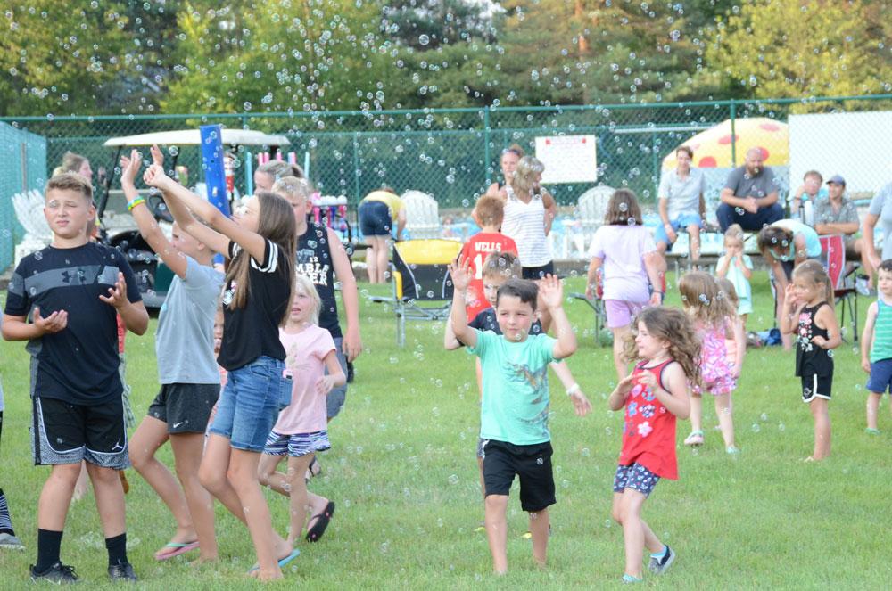 Kids Running Around In Bubbles
