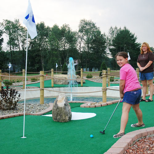 Young Girl Playing Mini Golf